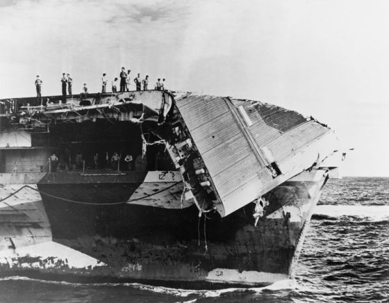 The bow of the U.S. Navy aircraft carrier USS Hornet (CV-12) showing damage received in a typhoon on 5 June 1945. The flight deck has been bent downwards over the bow and the plating torn away revealing the control position for the starboard catapult.