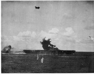 "U.S.S. HORNET during morning attack. ""Suicide"" dive bomber, in photo No. 1, has just crashed into the leading edge of the stack. Note smoke coming from hangar deck due to bomb hits aft."