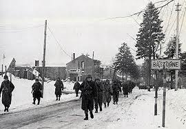 The 101st Airborne Division moving through the streets of Bastogne enroute to launch a counter attack against the Germans.......